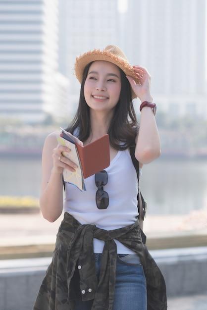 Mulher de solo asiática bonita do turista que sorri e que procura pelo ponto sightseeing dos turistas. Foto Premium