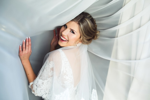 Mulher de sorriso com cortinas brancas Foto gratuita