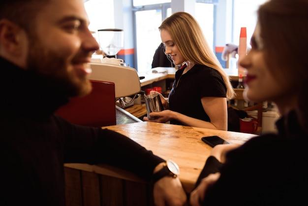 Mulher de sorriso positiva que prepara o café no contador. conceito de modelo de pessoas reais Foto Premium