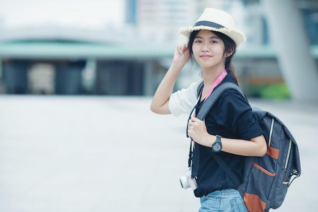 Mulher de sorriso que anda fora, jovem senhora que admira a vista da cidade com passagem e construções no fundo. Foto gratuita