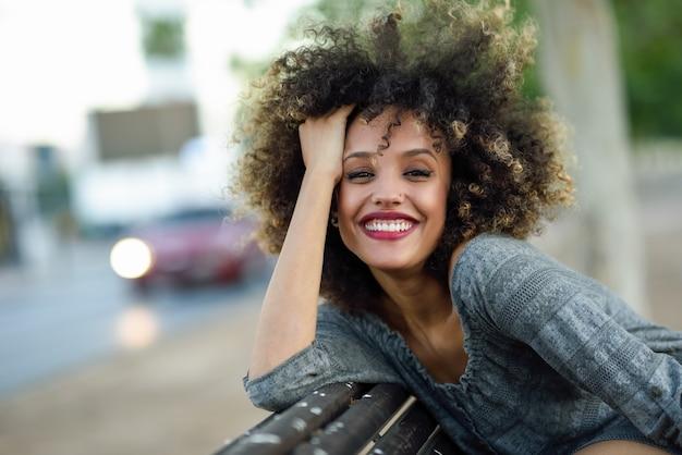 Mulher de sorriso que levanta com sua cabeça na parte de trás do banco de madeira Foto gratuita