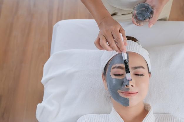 Mulher de spa, aplicação de máscara de argila facial. tratamentos de beleza. Foto Premium