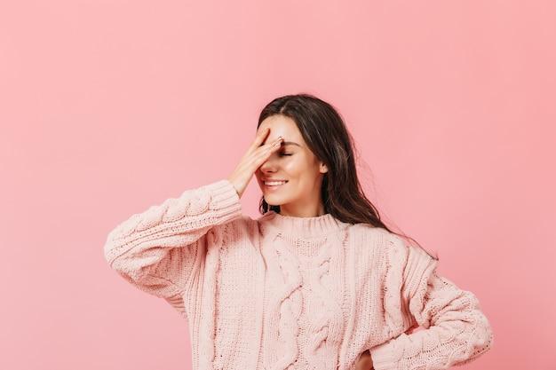Mulher de suéter rosa posando em fundo isolado. garota engraçada com sorriso faz facepalm. Foto gratuita
