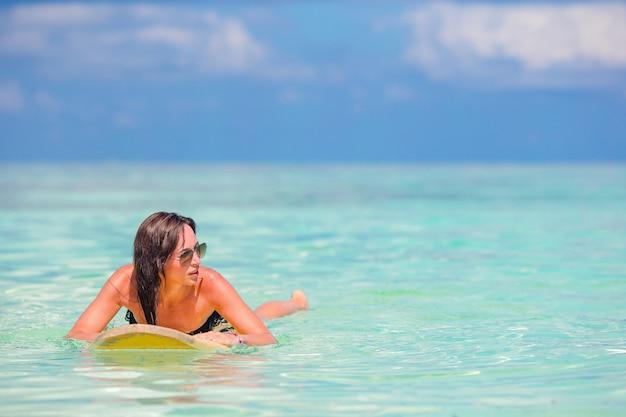 Mulher de surfista linda fitness surfando durante as férias de verão Foto Premium