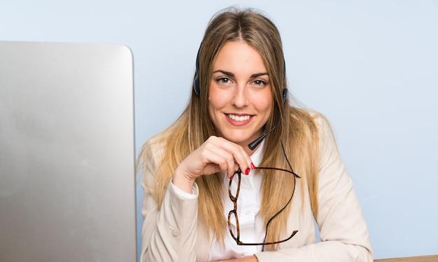 Mulher de telemarketing loira jovem e sorrindo Foto Premium