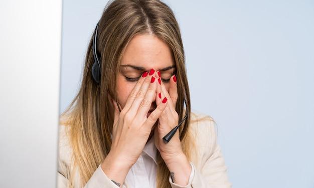 Mulher de telemarketing loira jovem sobre parede azul isolada e estressado Foto Premium
