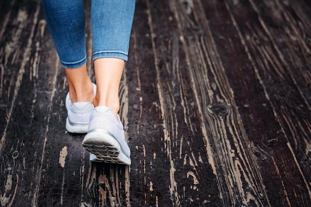 Mulher de tênis branco ir no chão de madeira Foto Premium