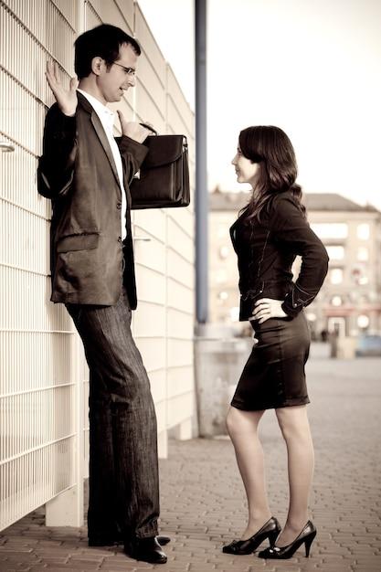 Mulher de terno preto pressionado homem de óculos com pasta para cercar na rua Foto Premium