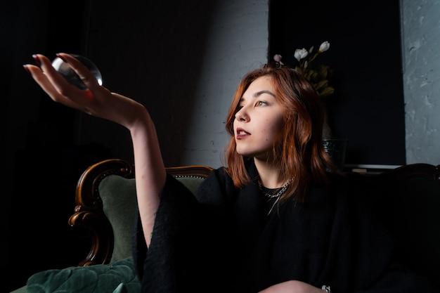Mulher de terno preto, segurando uma bola de cristal Foto gratuita