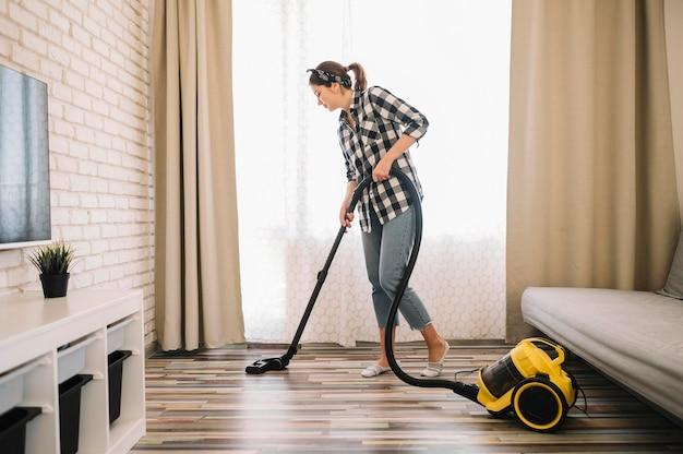 Mulher de tiro completo limpando a sala de estar Foto gratuita