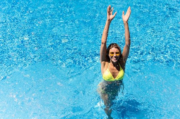 Mulher de tiro completo na piscina Foto gratuita