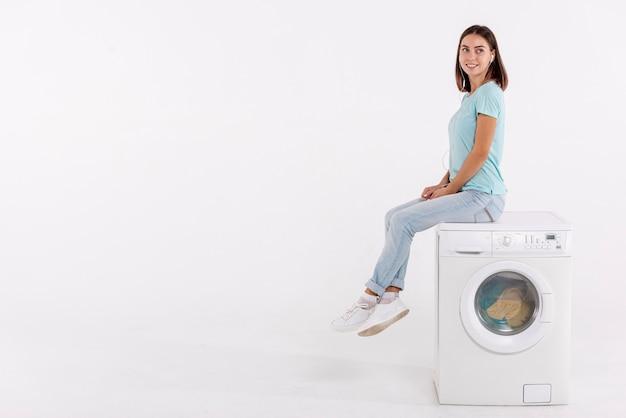 Mulher de tiro completo posando na máquina de lavar roupa Foto Premium
