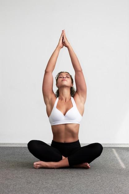 Mulher de tiro completo relaxante com pernas cruzadas Foto gratuita