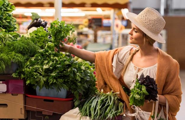 Mulher de tiro médio à procura de vegetais Foto gratuita