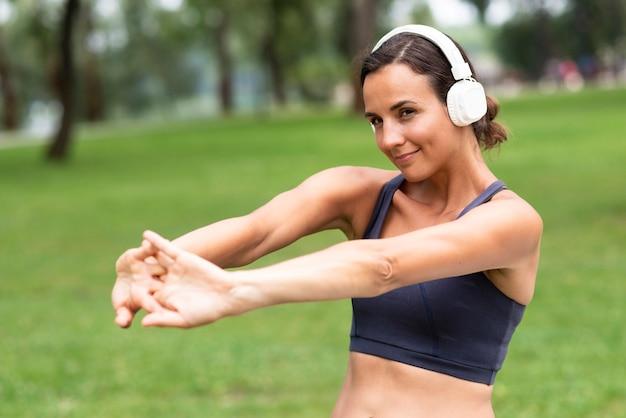 Mulher de tiro médio com fones de ouvido, esticando os braços Foto gratuita