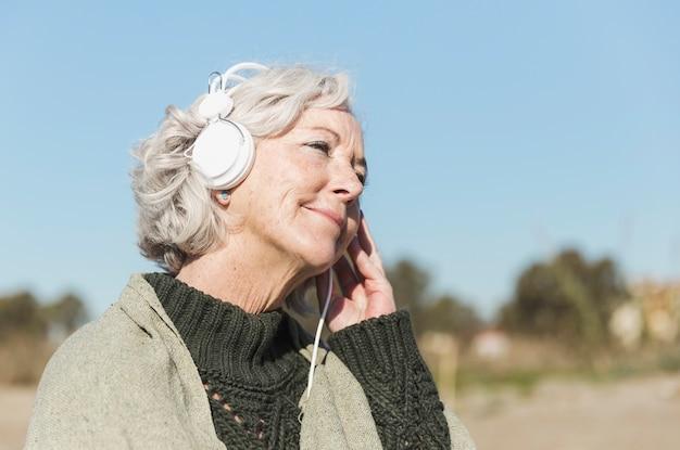 Mulher de tiro médio com fones de ouvido Foto gratuita