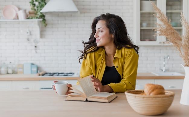 Mulher de tiro médio com livro e xícara de café Foto gratuita
