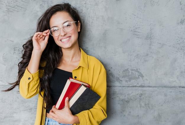 Mulher de tiro médio com óculos e livros Foto gratuita