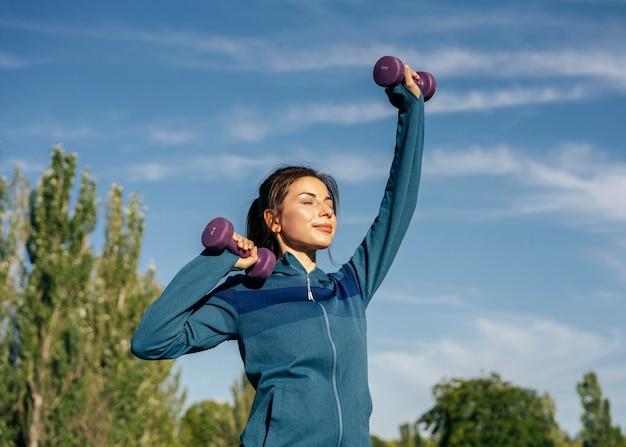 Mulher de tiro médio praticando com halteres Foto gratuita