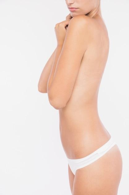 Mulher de topless, cobrindo o peito com os braços Foto gratuita