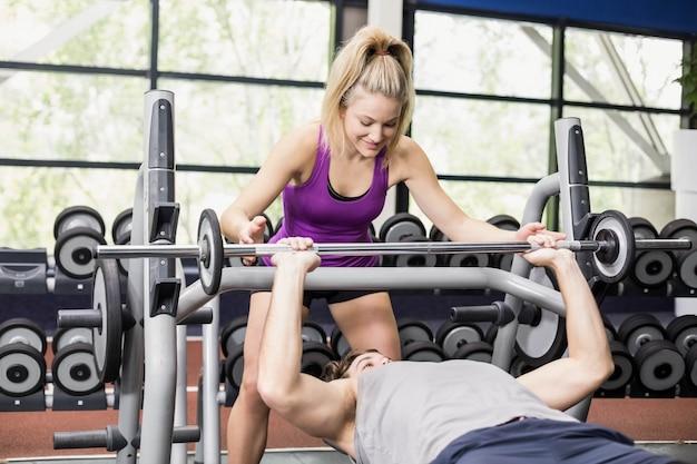 Mulher de treinador ajudando o homem atlético no ginásio crossfit Foto Premium