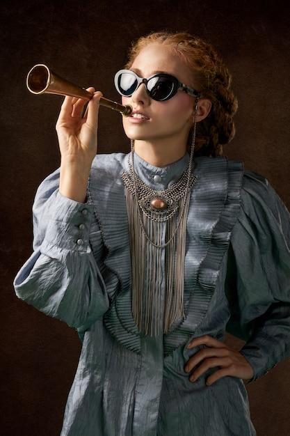 Mulher de vestido azul de mangas compridas, segurando trompete Foto gratuita