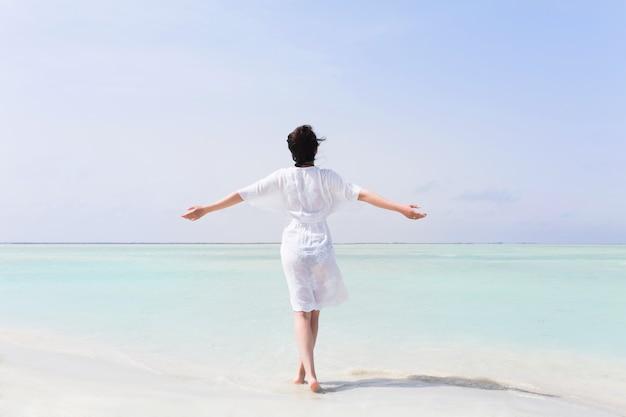Mulher de vestido branco com as mãos levantadas Foto Premium