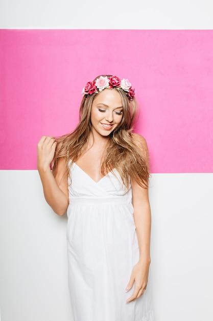 Mulher de vestido branco de algodão com flores no cabelo sorrindo Foto gratuita