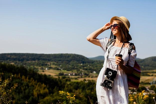 Mulher de vestido branco e câmera olhando para longe Foto gratuita