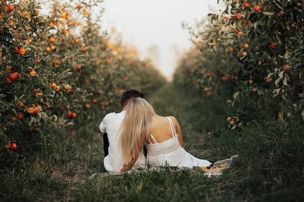 Mulher de vestido branco e homem de camisa branca estão fazendo piquenique no jardim de maçãs. Foto Premium