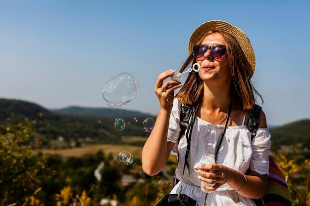 Mulher de vestido branco, fazendo bolhas de sabão Foto gratuita