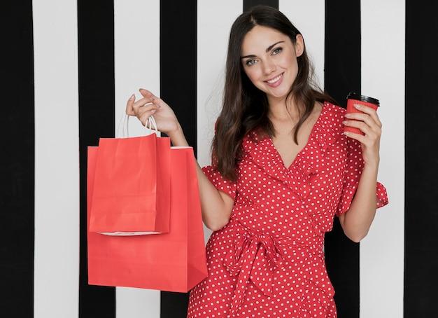 Mulher de vestido com café e sacolas de compras, sorrindo para a câmera Foto gratuita