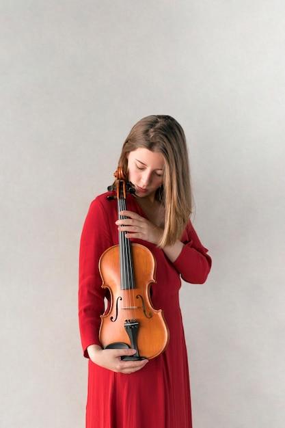 Mulher de vestido posando com violino Foto gratuita