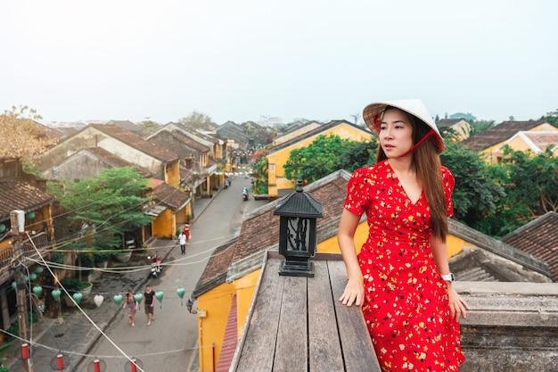 Mulher de viagens nas ruas de hoi an, vietnã Foto Premium