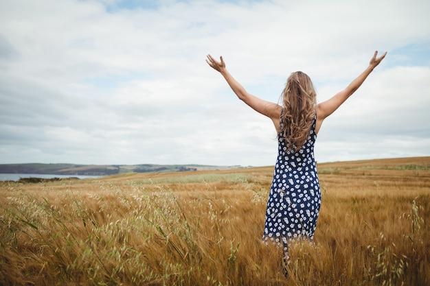 Mulher de visão traseira em pé com os braços estendidos Foto gratuita