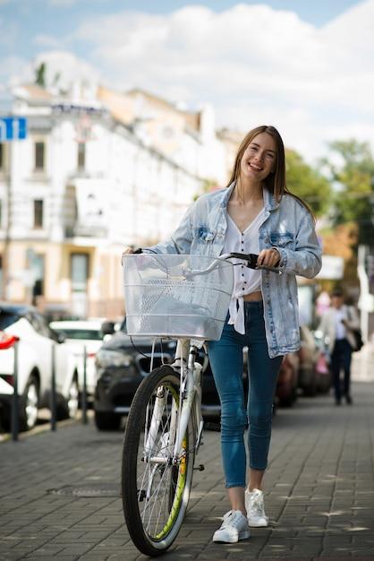Mulher de vista frontal andando ao lado de sua bicicleta Foto gratuita