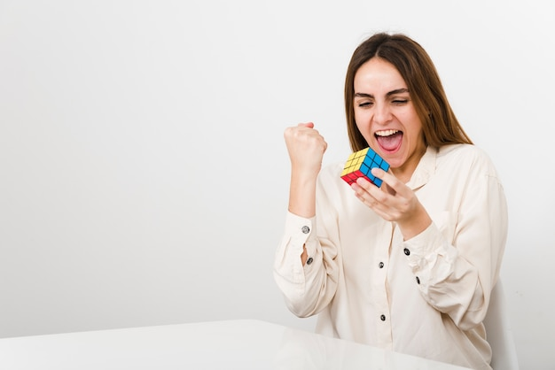 Mulher de vista frontal resolveu rubiks cubo Foto gratuita