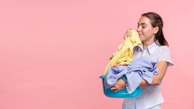 Mulher de vista lateral, cheirando a roupa limpa Foto Premium