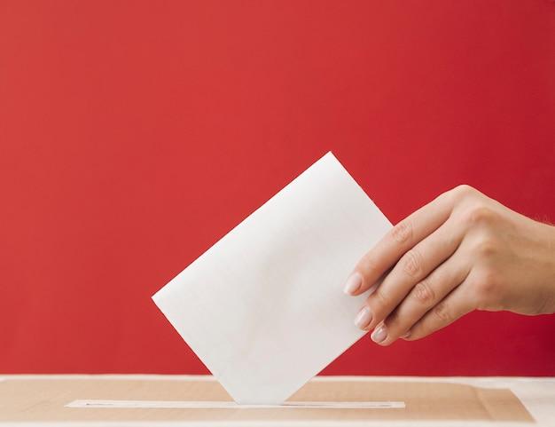 Mulher de vista lateral, colocando uma cédula em uma caixa com fundo vermelho Foto gratuita