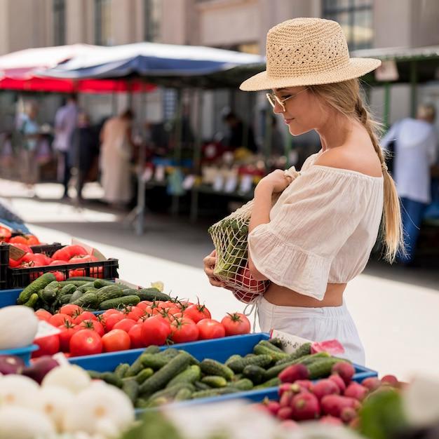 Mulher de vista lateral usando sacola orgânica para vegetais Foto gratuita