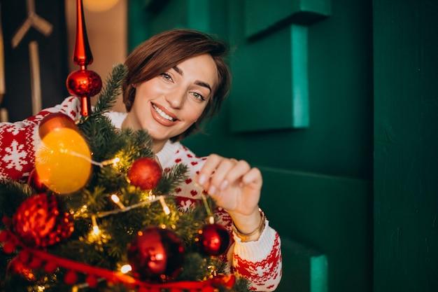 Mulher decorando a árvore de natal com bolas vermelhas Foto gratuita
