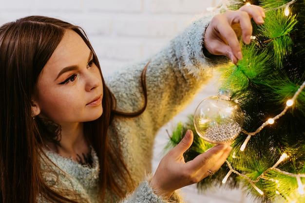 Mulher decorando a árvore de natal Foto gratuita