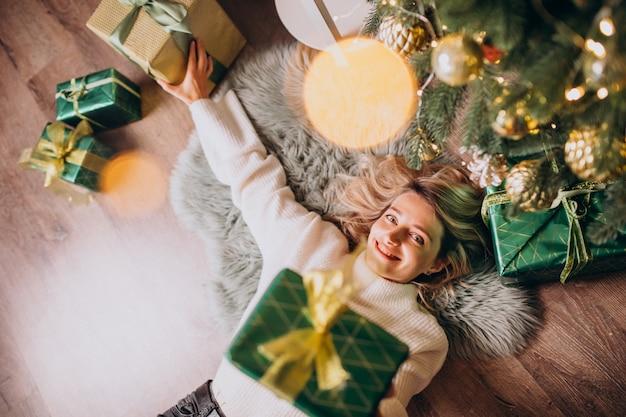 Mulher deitada debaixo da árvore de natal com presentes Foto gratuita