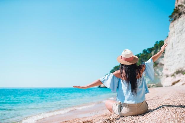 Mulher deitada na praia aproveitando as férias de verão, olhando para o mar Foto Premium