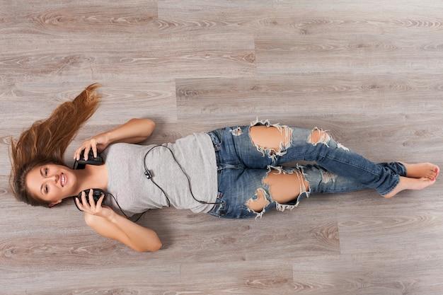 Mulher deitada no chão com fones de ouvido Foto gratuita