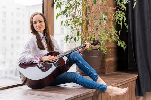 Mulher dentro de casa tocando violão Foto gratuita