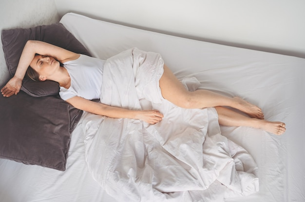 Mulher deprimida, atormentada por um sono inquieto, está exausta e sofre de insônia, pesadelos ou pesadelos, problemas psicológicos. cama ou colchão desconfortável e inconveniente. falta de dormir Foto Premium