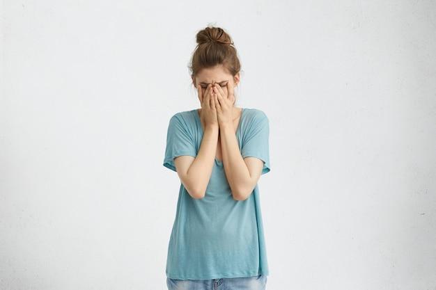 Mulher deprimida e decepcionada com coque de cabelo vestindo uma camiseta azul solta cobrindo o rosto com as mãos, estando cansada e exausta. mulher desesperada com depressão, escondendo o rosto chorando com as mãos Foto gratuita