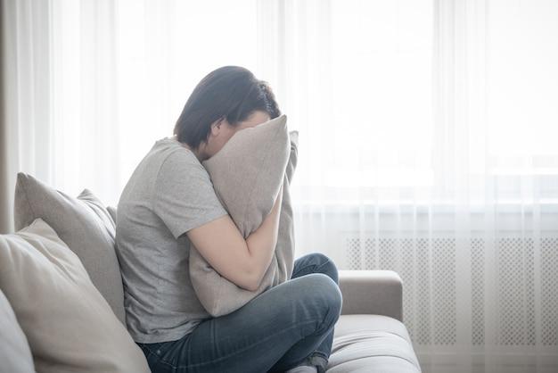 Mulher deprimida triste chorando no conceito de travesseiro, solidão e tristeza Foto Premium