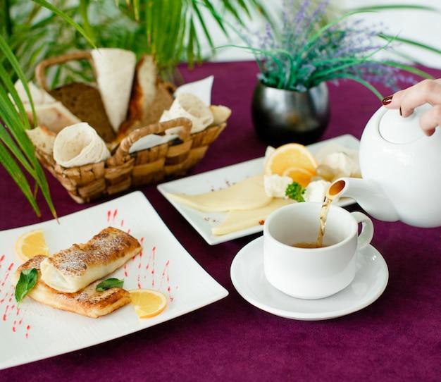Mulher derramando chá de bule no café da manhã com crepes Foto gratuita